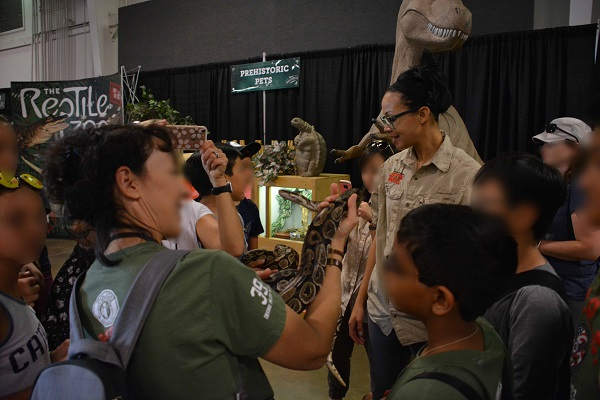 Scout troop leader and troop handle python at Imaginology