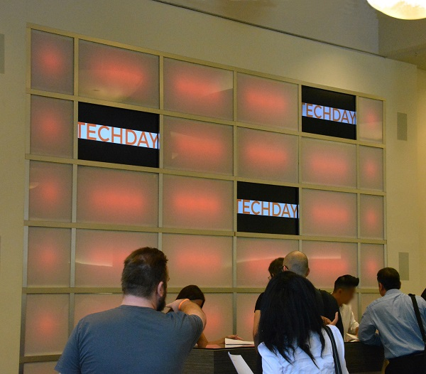 TechDay LA attendees sign in near an orange lighted wall with the word TECHDAY displayed