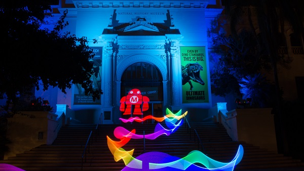 Nighttime building lit up with LED light art and Maker Faire® robotic logo