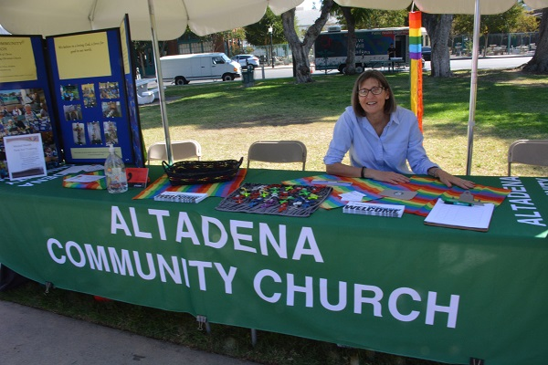 Woman at Altadena Community Church table with rainbow bunting