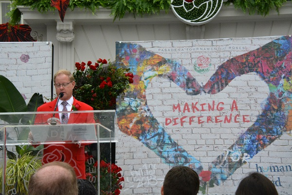 """Tournament of Roses Presdient Lance Tibbet reads from lectern with """"Making a Difference"""" banner behind him"""
