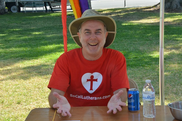 man in red Southern Calfiornai Lutheran Church T-shirt at table