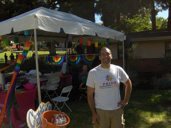 SGV Pride VP Aaron Saenz near tent with rainbow bunting