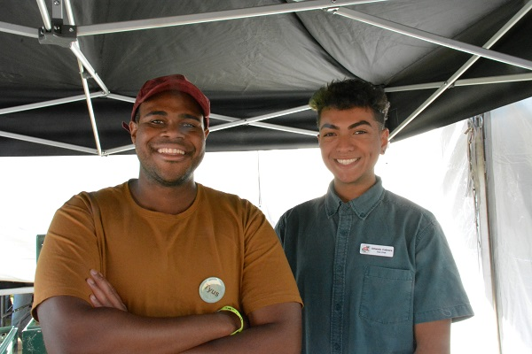 Engineering students Tyus Robinson and Orlando Cabrera staff the merchandising tent for the Cal Poly Rose Float
