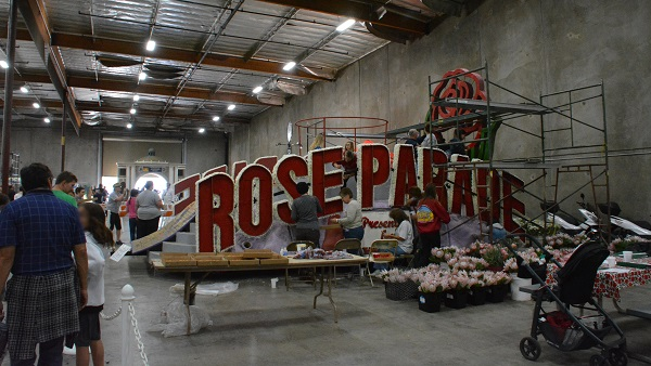 "Staffers decorate ""Rose Parade"" sign at Phoenix Decorating Company facilty"