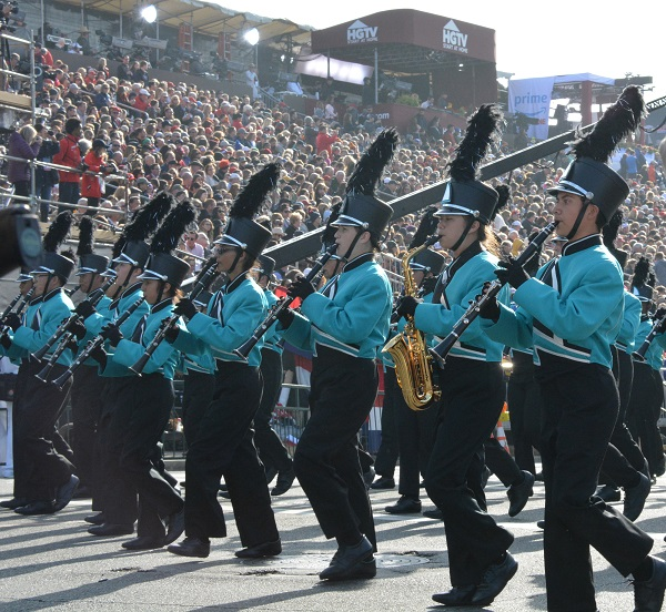 BOSS musicians in black slacks and aqua jackets play brass instruments before the reviewing stand