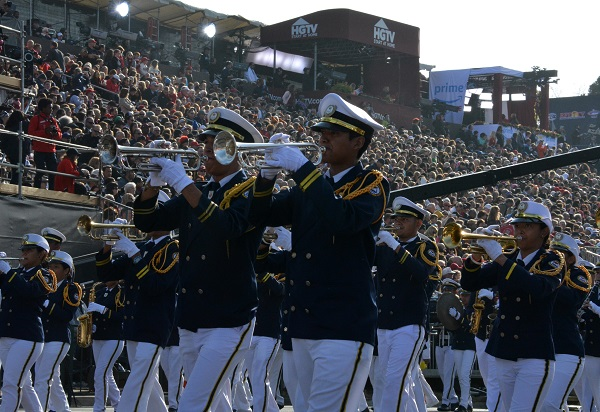 Banda De Musica musicians in navy blazers with white pants and caps playing brass instruments at the reviewing stand