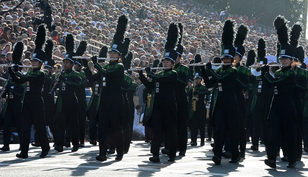 Homestead High musicians in black uniforms playing flutes at reviewing stand
