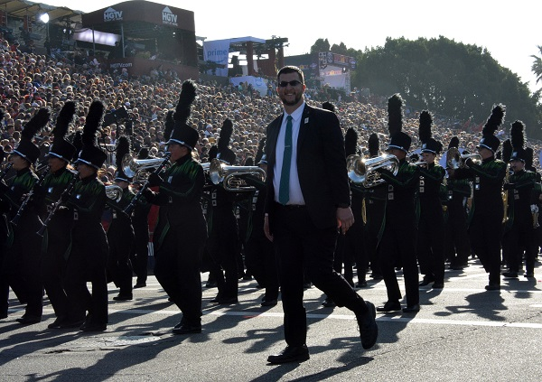 Homestead High band director in black suit with a green tie marches with his musicians in 129th Rose Parade