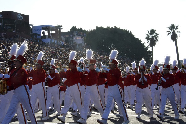 Pasadena City College Tournament of Roses Honor Band in white slacks and red jackets, playing as they walk by the reviewing stand