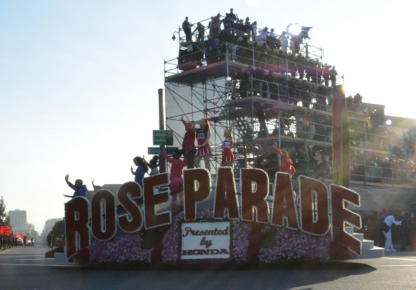 Rose Parade banner float with riders goes by TV corner