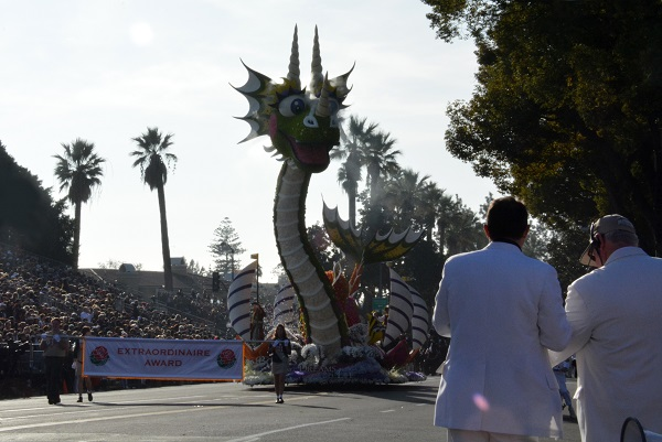 """Sea monster float with """"Extraordinaire"""" award banner appraches TV Corner as two White Suiters watch"""