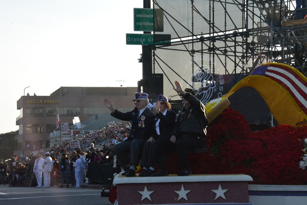 Three veterans wave from the float