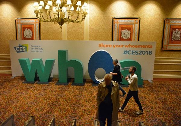 "CES 2018 attendees walk by a ""Whoa"" sign"