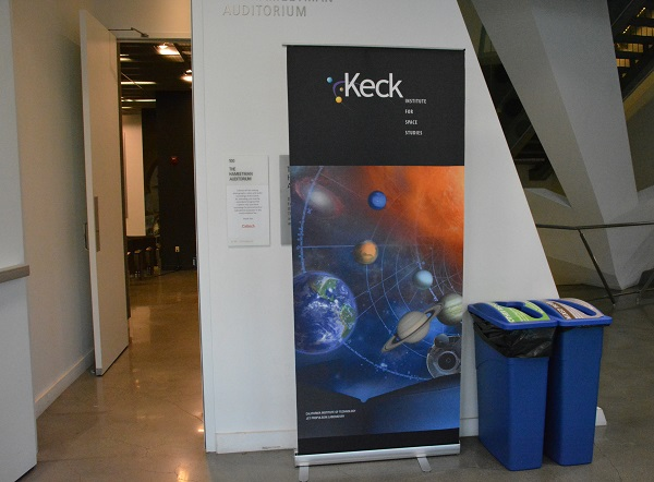Keck Institute sign advertises AR and VR symposium next to white wall