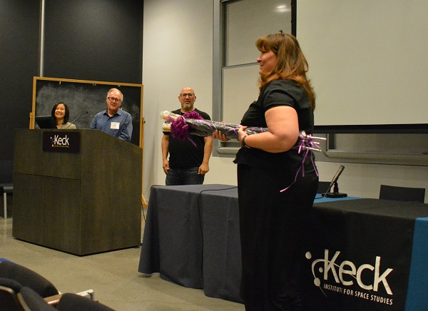 Michele Judd of Keck Institute for Space Studies comes onstage with gift-wrapped gift umbrellas