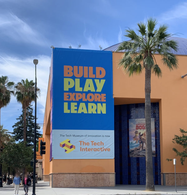 """The Tech exterior with palm tree and blue banner that says, """"Build, Play, Explore, Learn""""."""